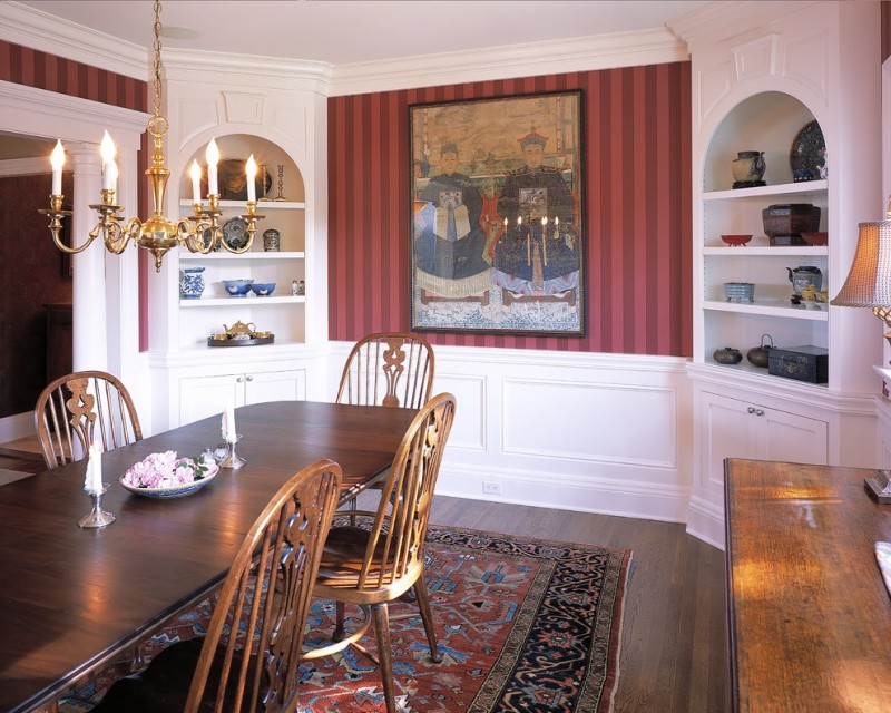 built in corner cabinets and shelves in white beautiful China painting in the center wood dining table wood dining chairs traditional motif area rug dark toned wood floors