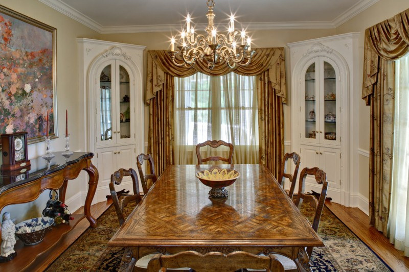 built in corner cabinets in white luxurious gold toned draperies chandelier with metal brush dark finished wood dining tables handcrafted dining chairs wood hall console