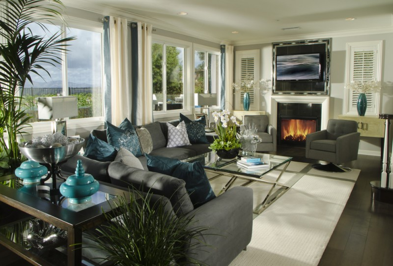 classic living room design with gray walls and a standard fireplace turquoise pillow throws and ornaments and vases black and white curtains
