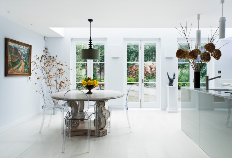 contemporary dining room in white white round top dining table clear acrylic French style dining chairs white ceramic tiles floors French door with glass panels