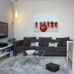 Contemporary Family Room With Gray Walls And A Wall Mounted TV Black Sofa White Painted Chair With Gray Pillow Throws Gray Rug Granite Tiles Floors