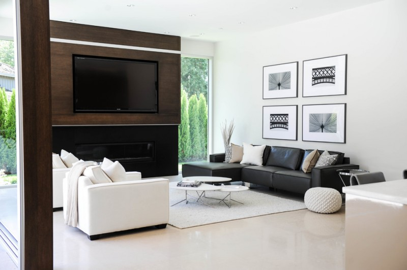 contemporary living room idea black leather sofa with decorative pillows white leather sofa with white accent pillows white area rug white floors large wood media wall modern black fireplace