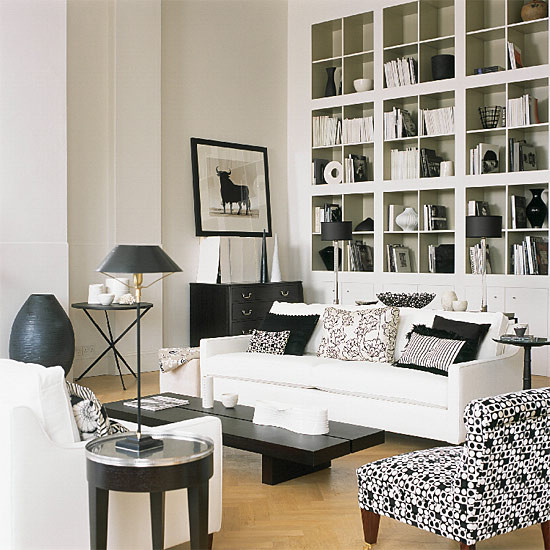contemporary living room soft white sofas with black and white accent pillows solid black coffee table black white chair without armrest pale toned wood floors round glass top side table