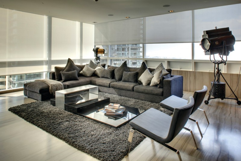 contemporary living room with dark gray couch and chairs and carpet light toned wooden floor black and white pillow throws modern coffee table