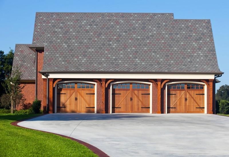 craftsman garage door three car garage red brick curved driveway wooden trim wooden door grey roof