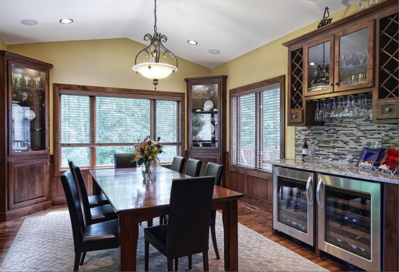 dark finished wood corner cabinets dining room with clear glass door dark toned wood dining table black leather dining chairs white area rug dark toned wood floors traditional pendant lamp