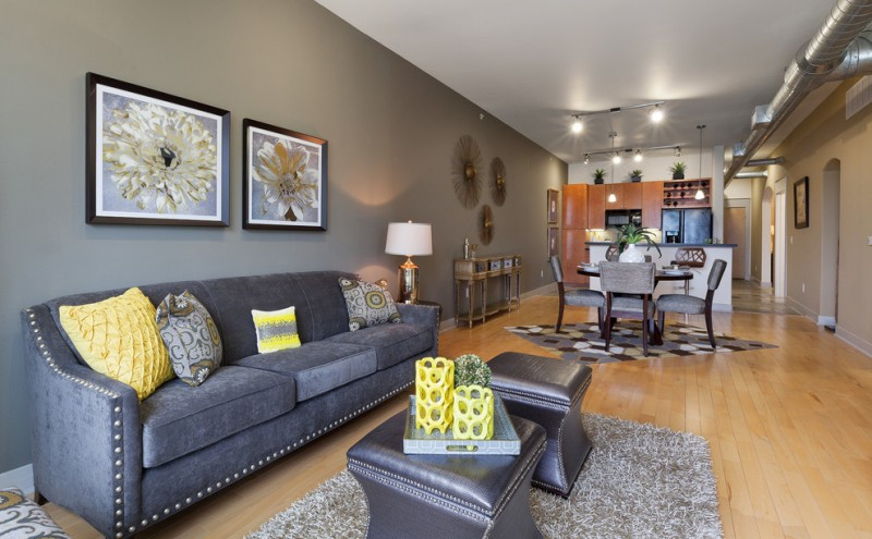 dark gray sofa and carpet lamp table gray dining room set geometric rug light toned wooden floor multicolored pillow throws wooden table and cabinets