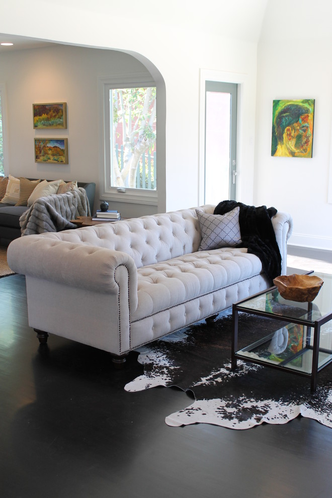 eclectic and simple living room white tufted sofa with a throw pillow and black blanket glass coffee table with black trims cowhide area rug black laminated floors