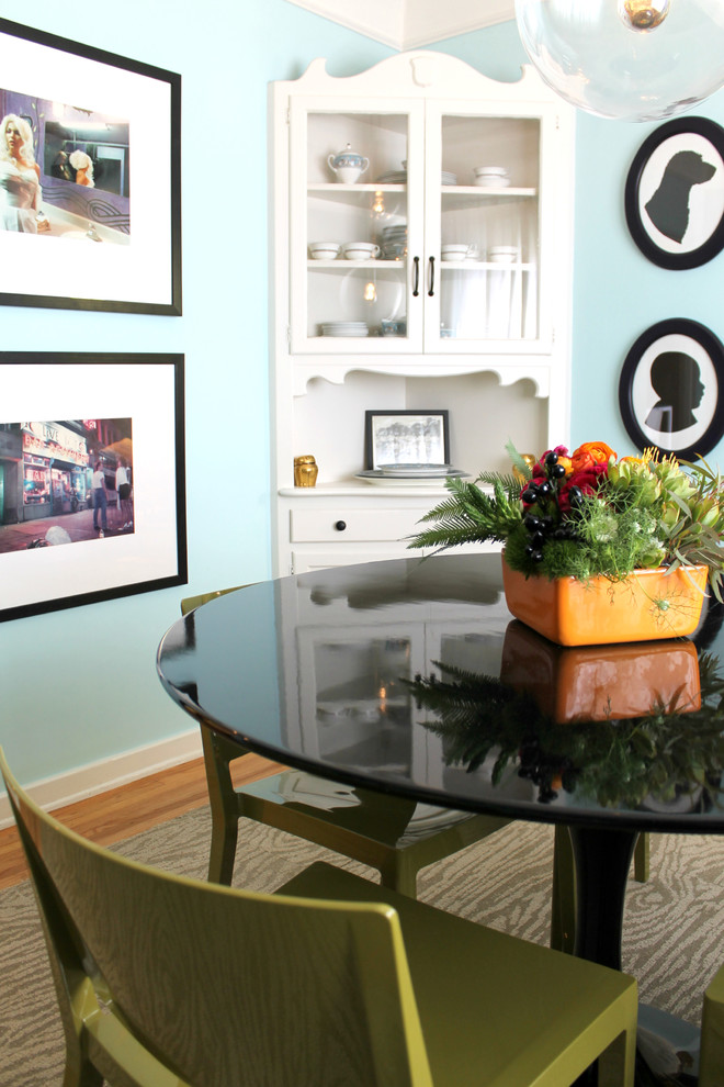 eclectic dining room idea blue walls built in corner cabinet in white some artistic photography some wall arts glossy black dining table in round shape medium toned wood floors