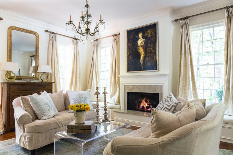 elegant formal living room with medium tone hardwood floors, a ribbon fireplace, a stone fireplace surround, white walls and brown floors