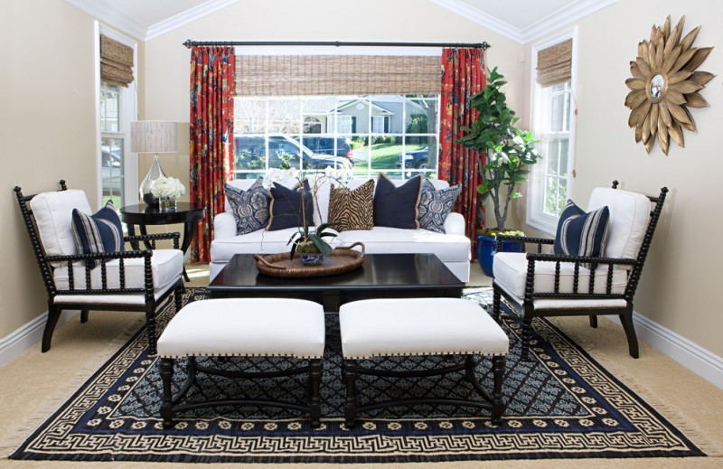 ethnic living room set Ottoman style area rug in dark blue modern white sofa with patterned throw pillows red draperies with motifs beige walls decorative wall art