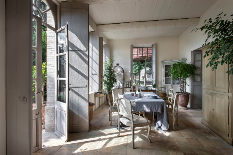 farmhouse dining room idea light grey corner cabinet light grey barn style door terracotta floors light cream walls pale toned wood diningg chairs blue covered dining table