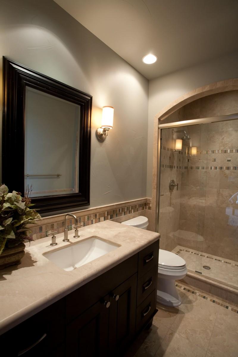 framed mirror granite countertop under mount sink dark vanity mosaic tile arched shower area wall sconce