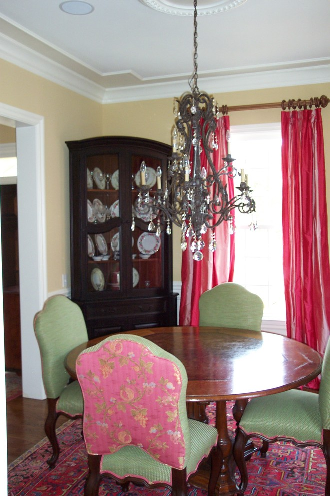 green pink dining chairs round shaped wood dining table area rug with traditional motif dark finished corner cabinets with wider glass door pink draperies antique crystal chandelier