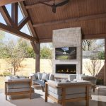 Grey Outdoor Cushions Stone Fireplace TV Gas Fireplace Sloped Ceiling Eposed Beams Ceiling Fan Wooden Craftsman Fence