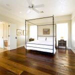 Large Rustic Master Bedroom With Beige Walls, Dark Hardwood Floors And Brown Floors White Fan White Painted Doors White Deck Wooden Walls