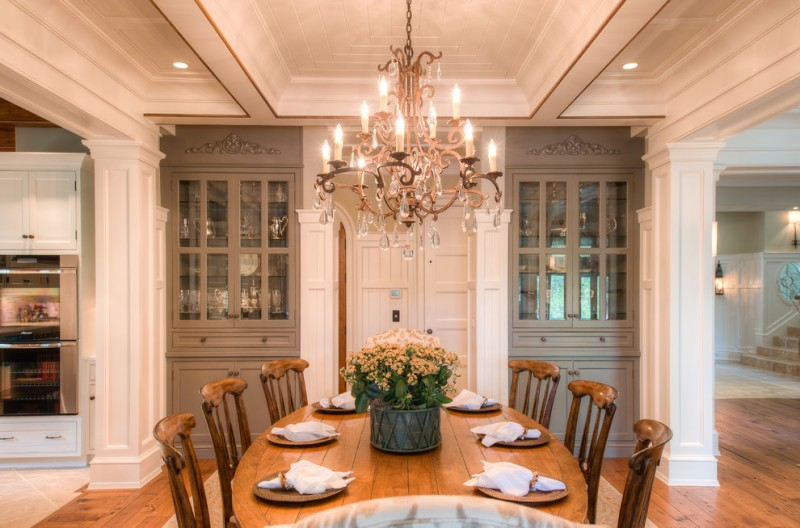 light grey corner cabinets with glass door luxurious cyristal chandelier wood dining chairs oval shaped wood dining table medium toned hardwood floors
