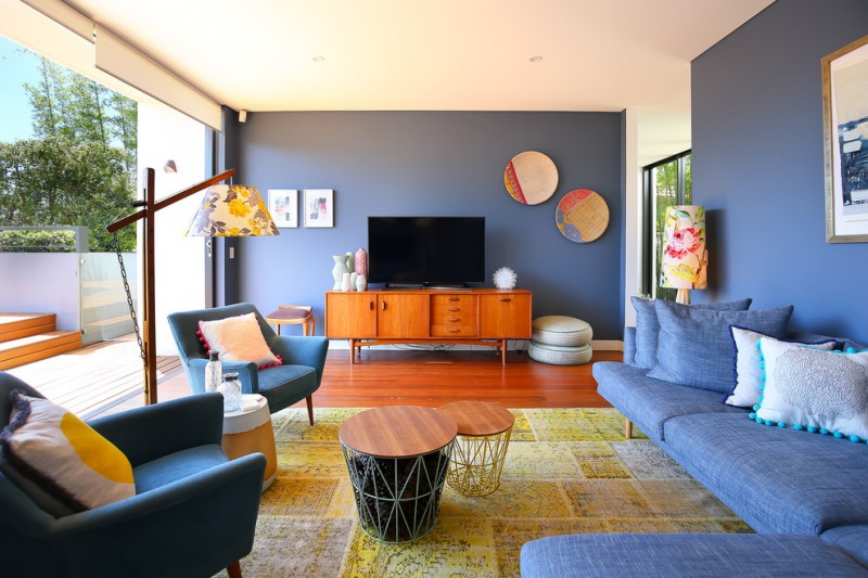 living room with blue sofa, chairs, wooden cabinet, flower cap floor lamp, tv, warm yellow rug, grey painted wall