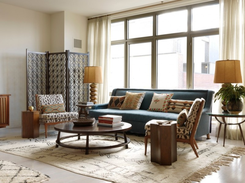 living room with patterned rug, blue sofa, black and white patterned chairs, partition, table lamp, side table