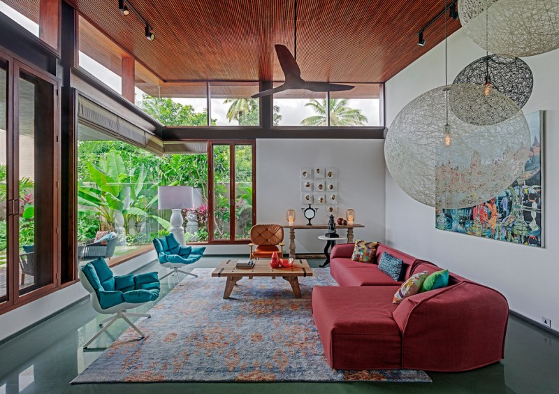 living room with ret sofa, wooden coffee table, blue soft cuhioned chairs, wooden chairs with red orange cushion