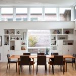 Media Wall In White Recessed Cabinets And Shelves Centered Glass Window Hardwood Dining Table Black Finished Dining Chairs Modern Hall Table With Decorative Vase Medium Toned Wood Floors