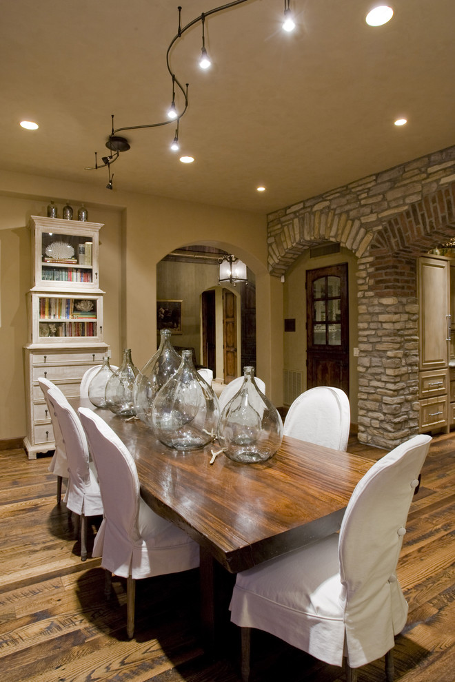 mediterranean style dining room French provincial dining chairs with short white slipcovers medium toned hardwood table medium toned wood floors white painted dining cabinet beige walls