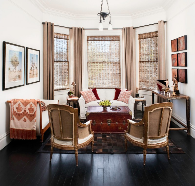 mid sized eclectic formal enclosed living room with white walls and dark hardwood floors chest table rattan blinds cream curtains multicolored rug