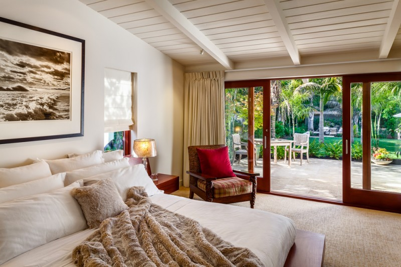 midcentury bedroom with beige walls and carpet brown chair red pillow throw white painted deck wooden ceiling outdoor table set table lamp beige blinds