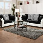 Modern Living Room Black Sofa With White Accents Black Love Seat With White Accents Black And Zigzag Accent Pillows Oval Shaped Clear Glass Top Table Grey Area Rug Medium Toned Wood Floors