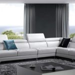 Modern Living Room Idea White Sectional With Adjustable Headrests And Metal Bases Black And Blue Throw Pillows Fluffy Grey Area Rug High End Coffee Table With Dark Glass Top
