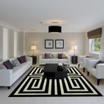 Modern Living Room Soft White Sofas With Accent Pillows Two White Chairs Modern Black Coffee Table With Decorative Vase Monochromatic Area Rug White Floors Light Grey Walls
