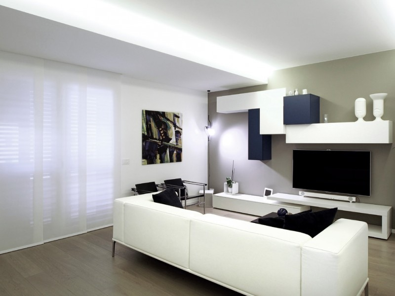 modern white sofa with solid black throw pillows modern industrial chairs with black back rests high end center table in white white media console floating storage units in white and dark blue