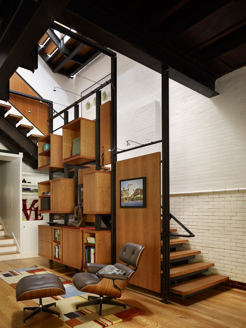 open staircase cubbies wooden floor brick wall lounge area rug covered ceiling brown cabinet