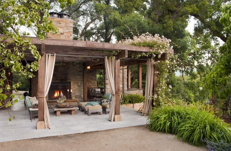 pergola stone fireplace stone chimney outdoor cushions outdoor curtain wooden coffee table tiled stone paving patio flowers