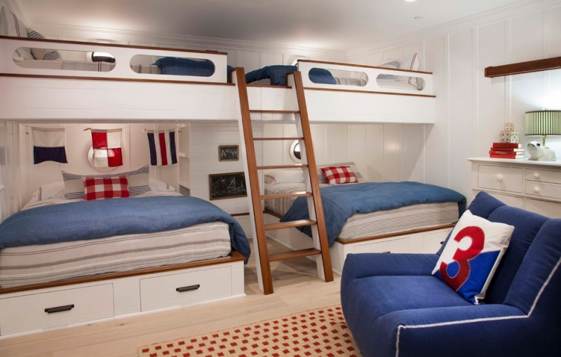 queen size bunk beds blue coastal style bedroom blue comfy couch square patterned rug drawers table lamp small circle windows storage under the bed