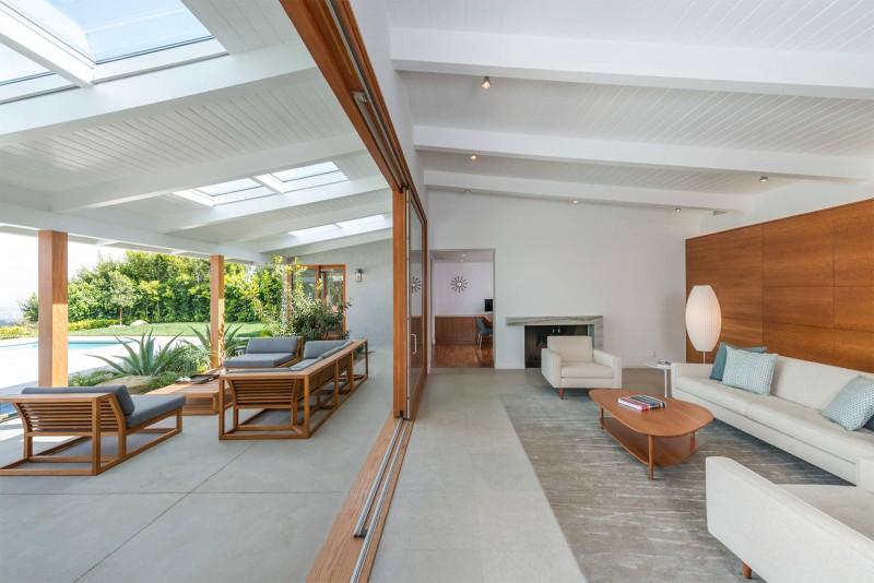 sloped ceiling wooden ceiling white sectional sofa glass sliding door area rug lotus floor lamp fireplace wooden wall wooden coffee table ceiling lights patio skylights