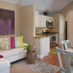 Small Contemporary Open Concept Living Room With Beige Walls And Medium Tone Hardwood Floors Multicolored Pillow Throws White Table Sets