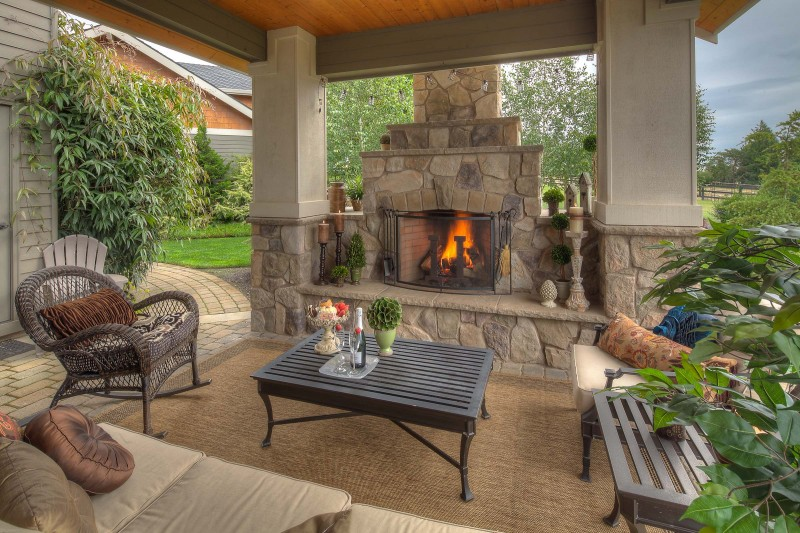 stone fireplace stone paving wicker chair outdoor cushions wooden bench wooden table area rug pergola