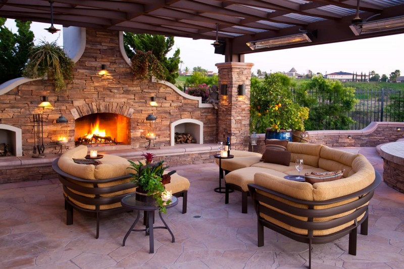 stone fireplace wood storage outdoor sectional sofastone paving round wooden table wall lamps corrugated plastic roof