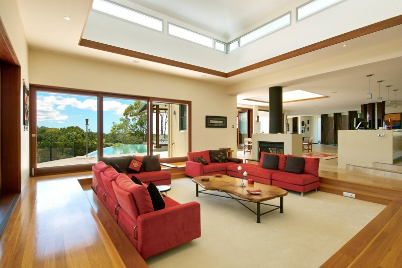 sunken living room raised ceiling wooden floor red sofa wooden coffee table recessed lights black throw pillow glass window fireplace ceiling lamps artwork decoration beige area rug