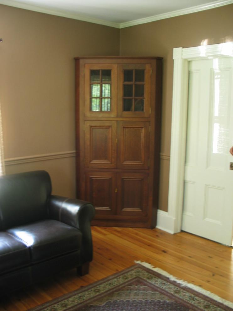 traditional corner cabinet in darker finishing black leather sofa medium toned wood floors dark area rug with traditional motifs