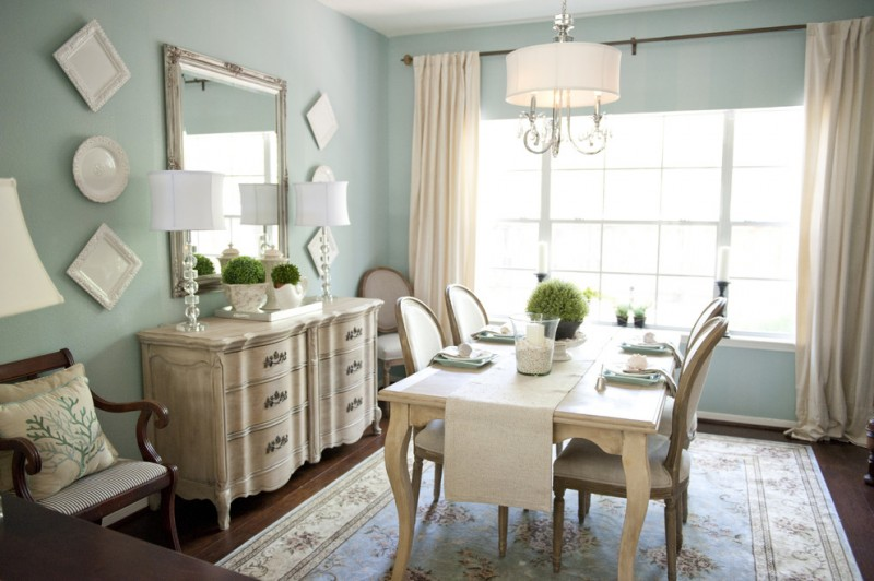 traditional dining room French style dining set traditional console with green plant arrangements large mirror with bronze frame blue walls dark tone wood floors