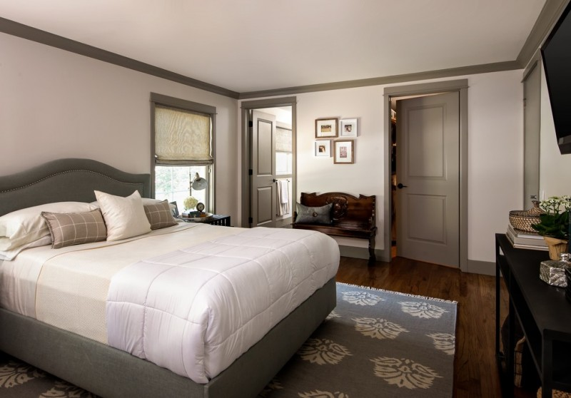 transitional bedroom with white walls and dark hardwood floors grey doors and trim grey bedding and rug wooden chair grey pillow throw black painted cabinet