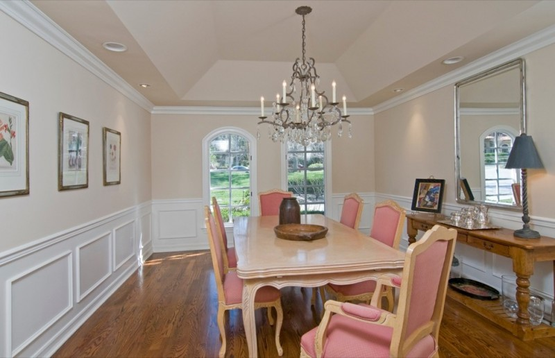 transitional dining room French style dining chairs with pink fabric pale toned wood dining table medium toned wood floors chandelier French windows wood hall table bronze framed mirror over the table