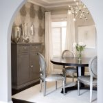Transitional Dining Room Silver Toned French Dining Chairs Black Round Top Wood Dining Table White Area Rug Dark Hardwood Floors Beige Walls