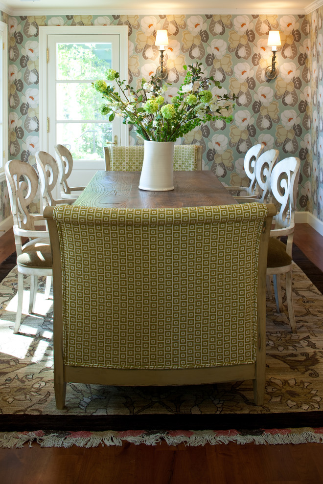 transitional dining room white painted French dining chairs large green cushions with motifs flower wallpaper area rug with motifs dark hardwood floors
