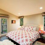 Trendy Bedroom Design With Beige Walls And Dark Hardwood Floors White Trim Iron Fences White Rug Table Lamp Round Table Dark Green Roman Shades