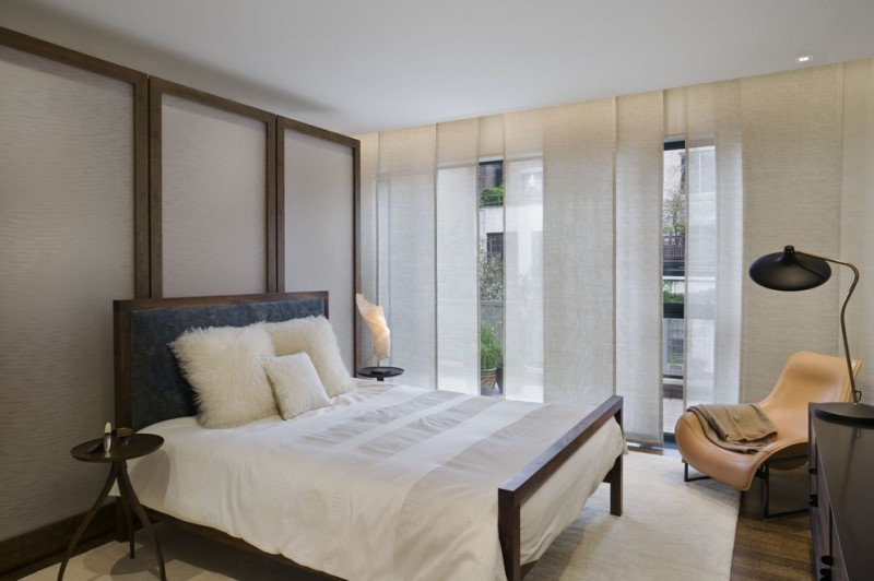 trendy bedroom with dark hardwood floors white sheet and pillow glass sliding doors with custom made window covers table lamp brown wooden cabinet