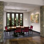 Trendy Dining Room With White Walls And Dark Hardwood Floors Kitchen Wooden Table Red Chairs Exposed Stone Wall Wall Artwork Gray Tiles