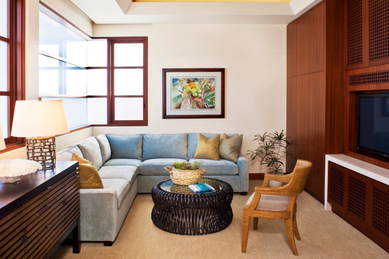 trendy family room design with beige walls, carpet and a built in media wall blue L shaped sofa wooden chair rattan coffee table wooden cabinet table lamp